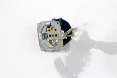 Electrician dismantling broken wall electric socket. On white co Stock Photography