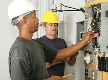 Electrician Diversity. An african american and a caucasian electrician working on a panel.  Actual electricians performing work according to industry safety and Royalty Free Stock Images