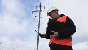 Electrician with documentation near high voltage line. In autumn day stock video footage
