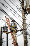 Electrician on electric pole. Electrician man (or cable guy) on electric pole to install new electric cable Stock Images