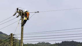 Electrician on electric pole Stock Photos