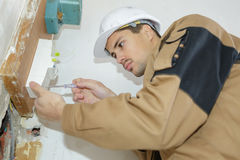 Electrician engineer checking data equipment in fuse-box. Electrician engineer checking data of equipment in fuse-box royalty free stock photos