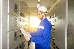Electrician Engineer on control panel with electric scheme. Maintenance of electrical equipments. Service worker tests automation system Stock Photos