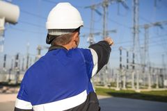 Electrician engineer on power electric station point to high voltage equipment royalty free stock photo