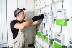 Electrician engineer works with screwdriver on fuse switch box. Electrician engineer in protective gloves and with flashlight works with screwdriver on fuse stock photography