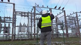 Electrician engineer take pictures on tablet near substation in winter stock footage
