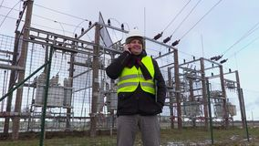 Electrician engineer talking on smart phone near substation in winter. In winter day stock video footage