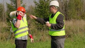 Electrician Engineer talking wth worker. On a sunny day stock video