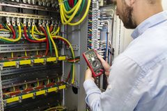 Electrician engineer testing cabling connection of high voltage power electric line in industrial distribution fuse board. Service man with multimeter. Tester stock image