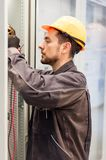 Electrician engineer tests electrical installations on relay pro. Electrician engineer tests electrical installations and wires on relay protection system. Bay Stock Photography