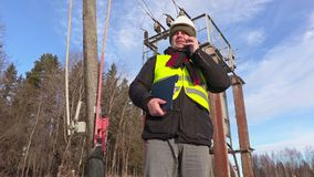 Electrician engineer using smart phone at transformer. In winter day stock footage
