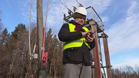 Electrician engineer using tablet near power lines and transformer. In winter day stock video