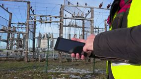 Electrician engineer using tablet near substation close up. In winter day stock video footage