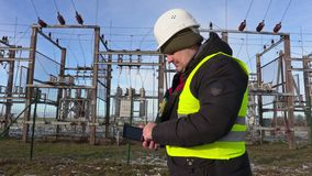 Electrician engineer using tablet near substation in winter stock video footage