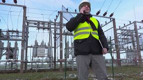Electrician engineer walking and using smart phone near substation in winter. Day stock video footage