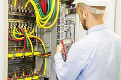 Electrician engineer in white helmet tests power voltage panel of three phase circuit. Service engineer electric with multimeter. Royalty Free Stock Photo