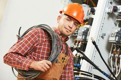 Electrician engineer worker. With cable in front of fuseboard equipment Stock Photos