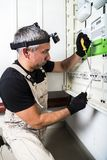 Electrician engineer works with screwdriver on fuse switch box close up. Electrician engineer in protective gloves and with flashlight works with screwdriver on stock photography