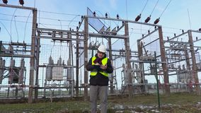 Electrician engineer writing and walking near substation in winter stock footage