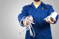 Electrician with equipment in the hands  on gray Royalty Free Stock Images