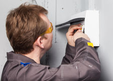 Electrician examining fuse box Royalty Free Stock Image