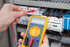 Electrician examining fusebox with resistance tester Stockfotos