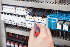 Electrician examining fusebox with screwdriver. Cropped image of male electrician examining fusebox with screwdriver Royalty Free Stock Photos