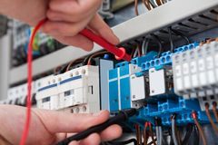 Free Electrician Examining Fusebox With Multimeter Probe Royalty Free Stock Photo - 43867895