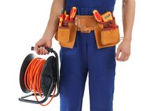 Electrician with extension cord reel and tools wearing uniform on white background. Closeup royalty free stock photography