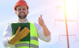 An electrician in the fields near the power transmission line. Stock Image