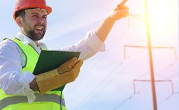 An electrician in the fields near the power transmission line. The electrician manages the process of erecting power lines. The mechanic in a helmet and a Stock Image