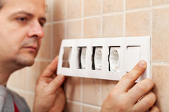 Electrician finished installing a wall fixture Royalty Free Stock Photos