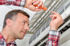 Electrician fitting air conditioning unit. Electrician fitting an air conditioning unit Stock Photography