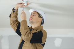 Electrician fitting ceiling light stock image