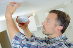 Electrician fitting fire alarm Royalty Free Stock Image