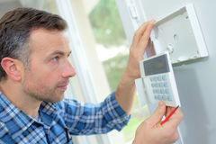 Electrician fitting intrusion alarm. Electrician fitting an intrusion alarm Stock Photos