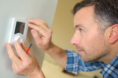 Electrician fitting thermostat system. Electrician fitting a thermostat system Royalty Free Stock Image