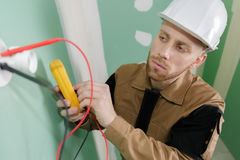 Electrician fitting wiring in house. Electrician fitting the wiring in a house Stock Image