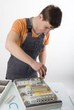 Electrician fixing cable in domestic electrical box Stock Photos