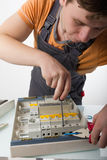 Electrician fixing cable in domestic electrical box Stock Image