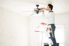 Electrician fixing a ceiling fan. Profile view of a male electrician stepping on a ladder and installing a ceiling fan in a house Royalty Free Stock Photography