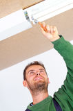Electrician fixing ceiling light Royalty Free Stock Image