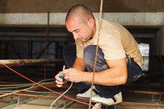 Electrician Fixing Devices. Electrician repairing electric devices using utensils and cables royalty free stock photo