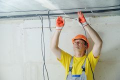 The electrician is fixing an electric cables. The electrician is fixing an electric cables to the ceiling stock images