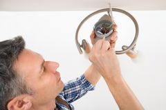 Electrician fixing light on ceiling Stock Image