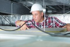 Electrician fixing neon on ceiling Royalty Free Stock Photo