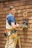 Electrician fixing outdoor light. Smiling man standing on ladder fixing outdoor light Royalty Free Stock Photos