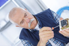 Electrician fixing outlet with screwdriver Royalty Free Stock Image