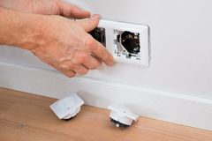 Electrician fixing socket Stock Image