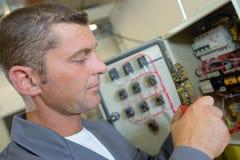 Electrician at fuse box. Electrician stock photos